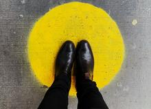 Feet standing on a yellow spot